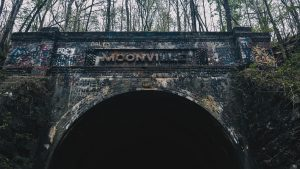 A photograph of the faded stone archway framing Moonsville Tunnel, an abandoned railway track. The tunnel is said to be one of the most haunted places in Ohio.
